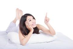 Mujer en destacar sonriente de la cama en el espacio de la copia Imagen de archivo