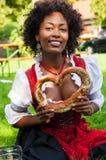Mujer en Dirndl con Pretzl bávaro Imagenes de archivo