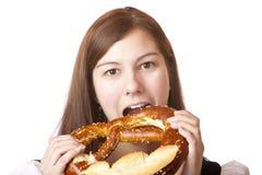 Mujer en Dirndl que come el pretzel de Oktoberfest Fotos de archivo
