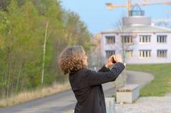 Mujer en el abrigo caliente que toma las fotos fotografía de archivo libre de regalías