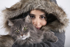 Mujer en el abrigo de pieles encapuchado que sostiene el gato Fotos de archivo