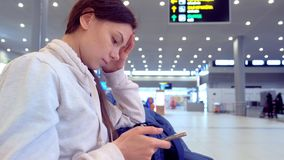 Mujer en el aeropuerto con un teléfono móvil en sus manos que esperan su vuelo, vista lateral almacen de metraje de vídeo