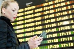 Mujer en el aeropuerto delante del tablero de la información del vuelo que comprueba su teléfono Imagen de archivo libre de regalías