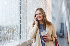 Mujer en el aeropuerto internacional que habla vía el teléfono móvil Fotos de archivo libres de regalías