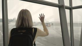 Mujer en el aeropuerto que mira el avión almacen de video