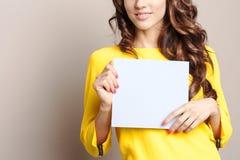 Mujer en el amarillo que lleva a cabo una muestra en blanco Fotografía de archivo libre de regalías