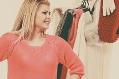 Mujer en el armario casero que elige la ropa Foto de archivo