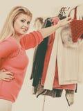 Mujer en el armario casero que elige la ropa Fotos de archivo