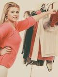Mujer en el armario casero que elige la ropa Imágenes de archivo libres de regalías