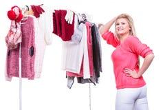 Mujer en el armario casero que elige la ropa, indecisión Foto de archivo libre de regalías