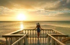 Mujer en el balcón que mira la puesta del sol hermosa imagenes de archivo