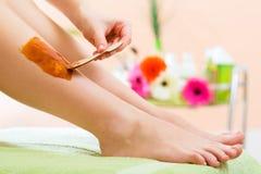Mujer en el balneario que consigue la pierna encerada para el retiro del pelo imágenes de archivo libres de regalías