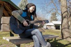 Mujer en el banco que toca la guitarra Imagen de archivo libre de regalías