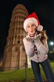 Mujer en el beso del aire del sombrero de Papá Noel que sopla cerca inclinado la torre de Pisa Foto de archivo libre de regalías