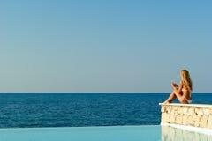 Mujer en el bikiní blanco que se sienta cerca de piscina del infinito Imágenes de archivo libres de regalías