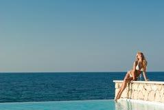 Mujer en el bikiní blanco que se sienta en el borde de la piscina Fotos de archivo