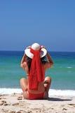 Mujer en el bikiní rojo que se sienta en la playa que ajusta el sombrero Imagenes de archivo
