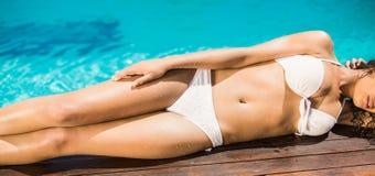 Mujer en el bikini blanco que miente en apilador de madera por el lado de la piscina Foto de archivo