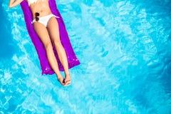 Mujer en el bikini blanco que miente en cama de aire en piscina Imagen de archivo libre de regalías