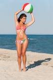 Mujer en el bikini joying con la pelota de playa colorida imágenes de archivo libres de regalías
