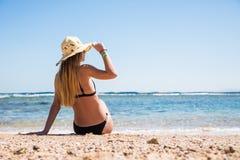 Mujer en el bikini negro que descansa sobre la playa en sombrero de paja cerca del mar fotografía de archivo
