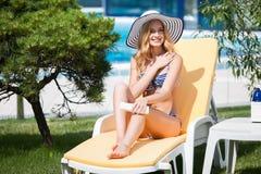 Mujer en el bikini que aplica la crema del bloque del sol en bronceada Imagenes de archivo
