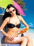 Mujer en el bikini que aplica la crema del bloque del sol en carrocería Imagen de archivo