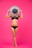 Mujer en el bikini que cubre su cara con el sombrero Foto de archivo libre de regalías