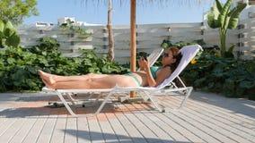 Mujer en el bikini que se relaja con smartphone en Sunbed en casa almacen de metraje de vídeo