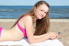 Mujer en el bikini rosado que miente en la playa con el teléfono móvil Imagen de archivo