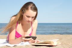 Mujer en el bikini rosado que miente en la playa con el teléfono móvil y BO Foto de archivo libre de regalías