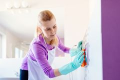 Mujer en el botón blanco del retrete de la limpieza del delantal imágenes de archivo libres de regalías