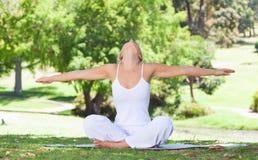 Mujer en el césped que hace ejercicios de la yoga Imagenes de archivo