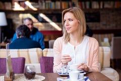 Mujer en el café de consumición del café, gozando de su café express Imagen de archivo libre de regalías