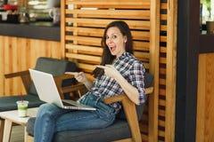 Mujer en el café de madera de la cafetería del verano de la calle del aire libre que se sienta en la ropa casual, trabajando en e foto de archivo