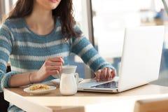 Mujer en el café que practica surf la red Imagenes de archivo