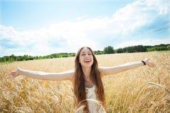 Mujer en el campo de trigo con los brazos outstretched Fotos de archivo
