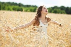 Mujer en el campo de trigo con los brazos outstretched Foto de archivo libre de regalías