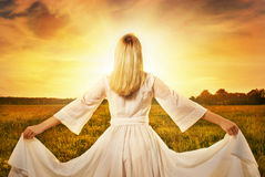 Mujer en el campo en la puesta del sol Foto de archivo libre de regalías