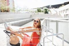 Mujer en el carro de la compra al aire libre Imagenes de archivo