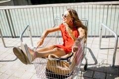 Mujer en el carro de la compra al aire libre Foto de archivo