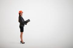 Mujer en el casco del desgaste formal y de la construcción que lleva a cabo los materiales i Fotografía de archivo