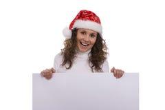 Mujer en el casquillo de la Navidad que sostiene informativo en blanco Fotografía de archivo libre de regalías