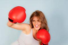 Mujer en el chaleco que lleva guantes de boxeo rojos Foto de archivo