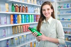 Mujer en el champú de compra de la farmacia Imagen de archivo