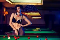 Mujer en el club de los billares que juega el billar Imágenes de archivo libres de regalías