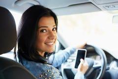 Mujer en el coche con el teléfono móvil Fotografía de archivo libre de regalías