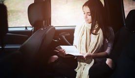 Mujer en el coche, concepto de la caída del otoño Muchacha bonita sonriente que lee un libro que se mueve en coche Foto de archivo libre de regalías