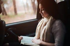 Mujer en el coche, concepto de la caída del otoño Muchacha bonita sonriente que lee un libro que se mueve en coche Imagenes de archivo