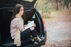 Mujer en el coche, concepto de la caída del otoño Muchacha bonita sonriente que lee un libro que se mueve en coche Imágenes de archivo libres de regalías